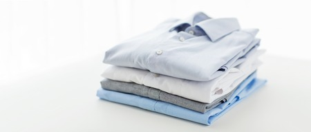 fashion clothes: ironing, laundry, clothes, housekeeping and objects concept - close up of ironed and folded shirts on table at home Stock Photo