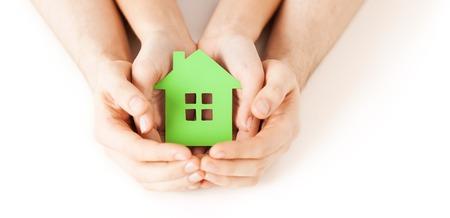 부동산 및 가족 홈 개념 - 녹색 빈 종이 집을 들고 남성과 여성의 손의 근접 촬영 사진
