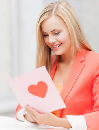 compliment: picture of woman holding postcard with heart shape.
