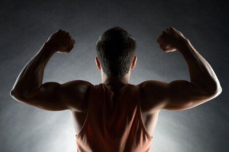 hombre fuerte: deporte, el culturismo, la fuerza y ??la gente concepto - jóvenes bíceps hombre que muestra sobre el fondo negro de la parte posterior Foto de archivo