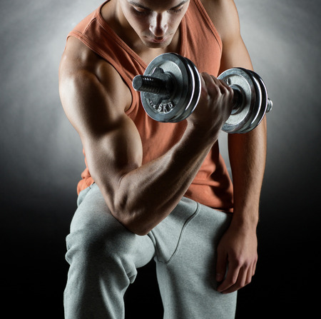 dumbbell: sport, bodybuilding, training and people concept - young man with dumbbell flexing muscles over gray background