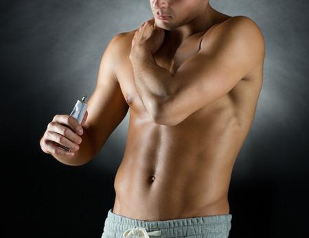 cuerpo hombre: deporte, el culturismo, la medicina y la gente concepto - joven de pie sobre fondo negro y la aplicación de gel de alivio del dolor en el hombro