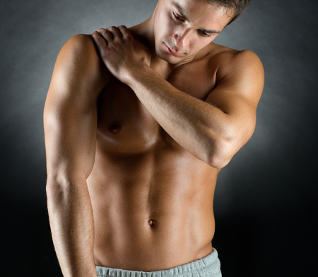 shoulders: pain relief, sport, bodybuilding, health and people concept - young man standing over black background Stock Photo