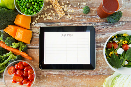 healthy eating, dieting, slimming and weigh loss concept - close up of diet plan on tablet pc screen and vegetables Foto de archivo