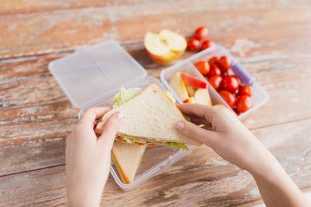 La alimentación saludable, el almacenamiento, la dieta y el concepto de la gente - cerca de la mujer con la comida en un recipiente de plástico en la cocina en casa Foto de archivo - 46389721