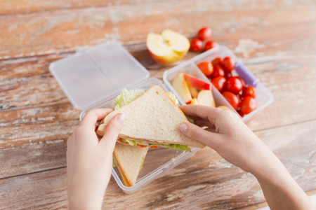 bocadillo: la alimentación saludable, el almacenamiento, la dieta y el concepto de la gente - cerca de la mujer con la comida en un recipiente de plástico en la cocina en casa