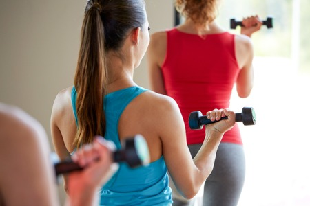 step fitness: fitness, sport, training, people and lifestyle concept - close up of women working out with dumbbells and flexing muscles in gym