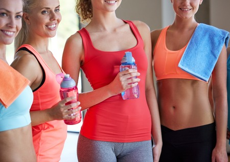 teamwork concept: fitness, sport, teamwork, people and lifestyle concept - group of women with bottles of water in gym