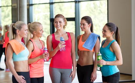 fitness, deporte, entrenamiento, gimnasio y estilo de vida concepto - grupo de mujeres con botellas de agua en el gimnasio