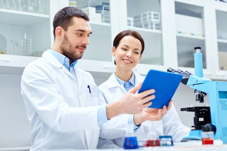 chemical laboratory: science, chemistry, technology, biology and people concept - young scientists with tablet pc and microscope making test or research in clinical laboratory Stock Photo