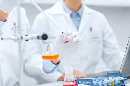 科学、化学、技術、生物学および人々 のコンセプト - ピペット充填テスト チューブ臨床研究室で研究を行う科学者の手のクローズ アップ