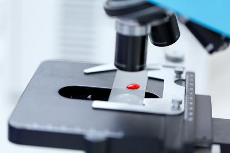 clinical laboratory: science, chemistry, biology, medicine and research concept - close up of microscope with blood test sample in clinical laboratory