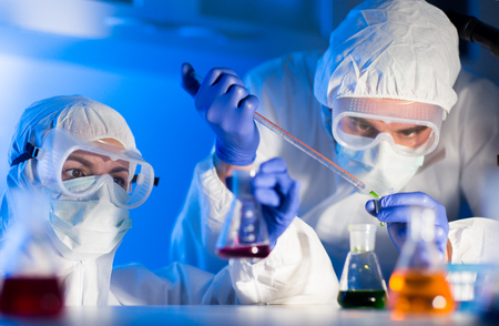 laboratorio: la ciencia, la química, la biología, la medicina y el concepto de la gente - cerca de los jóvenes científicos con pipetas y frascos que hacen prueba o investigación en laboratorio clínico