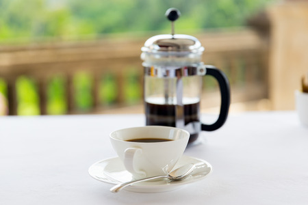 carafe: drinks, energetic, morning and caffeine concept - cup of black coffee and french press on table at restaurant