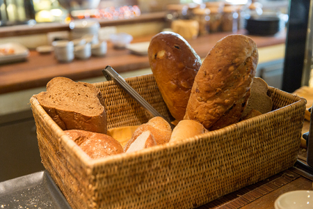 baked: bakery, baking, food and eating concept - basket with bread at restaurant