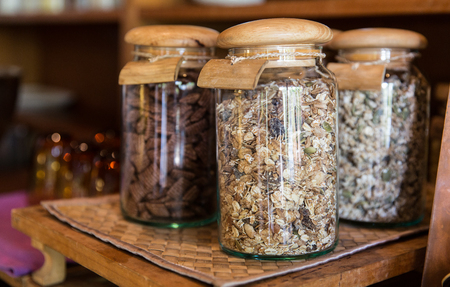 food storage: food, storage and eating concept - close up of jars with granola at grocery store