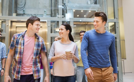 hot boy: education, high school, friendship, drinks and people concept - group of smiling students with paper coffee cups Stock Photo
