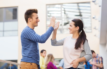 group of smiling students outdoors making high five Stock Photo