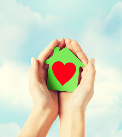 valor: closeup picture of female hands holding green paper house with red heart Foto de archivo