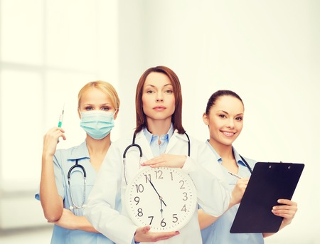 timezone: calm female doctor and nurses with wall clock and stethoscope
