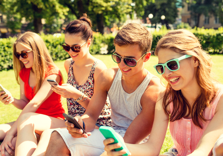 woman on phone: group of smiling friends with smartphones sitting on grass in park