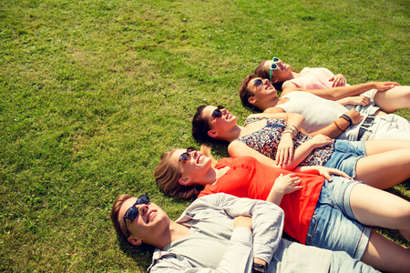 people relaxing: group of smiling friends lying on grass outdoors