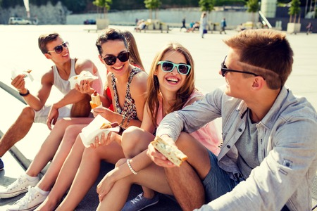 group of smiling friends in sunglasses sitting with food on city square Imagens