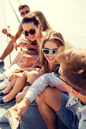 gente comunicandose: grupo de amigos sonrientes en gafas de sol que se sienta con la comida en la plaza de la ciudad Foto de archivo