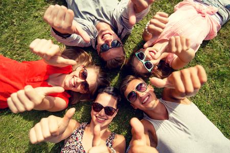 amistad: grupo de amigos sonrientes que mienten en hierba en círculo y que muestran los pulgares arriba al aire libre