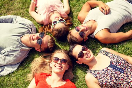 resting: group of smiling friends lying on grass in circle outdoors