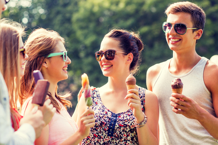 women friendship: group of smiling friends with ice cream outdoors