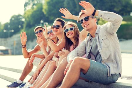 groep lachende vrienden zitten op stadsplein