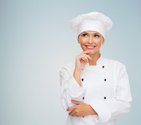asian cook: smiling female chef, cook or baker dreaming over gray background Stock Photo