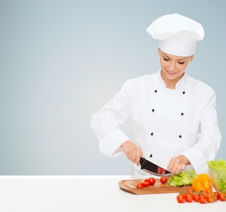 cuchillo de cocina: sonriendo cocinera, cocinero o panadero cortar vegetales sobre fondo gris