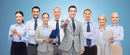 grupo de gente de negocios feliz apuntando a usted sobre fondo azul
