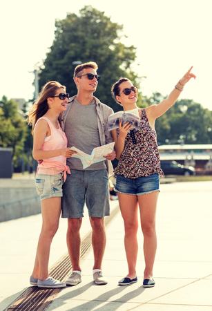 grupo de hombres: amigos sonrientes con el mapa y gu�a de la ciudad se�alar con el dedo al aire libre
