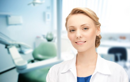 happy young female dentist with tools over medical office background