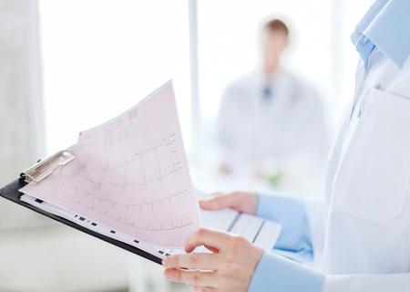 electrocardiograma: close up de portapapeles celebración femenino con el cardiograma