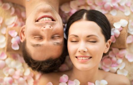 salon treatment: faces of couple in spa salon lying on the massage desks Stock Photo