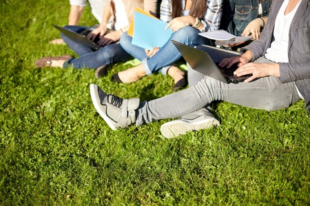 teen: close up of students with laptop computers and folders sitting on grass