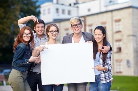 jovenes estudiantes: grupo de estudiantes adolescentes felices celebración de gran cartel en blanco blanco