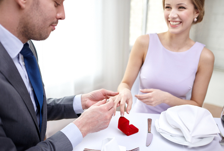 diamond ring: close up of man putting ring to his fiance finger at restaurant Stock Photo