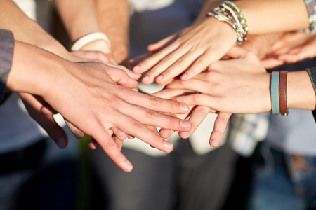 close up of students or teenagers with hands outdoors