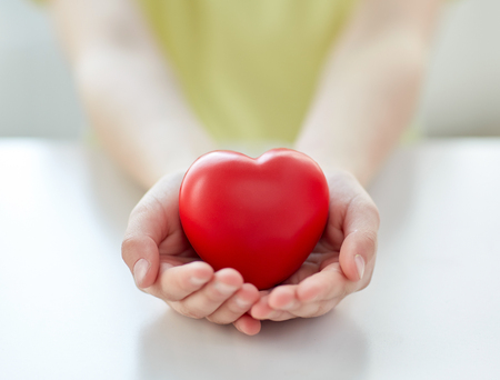 hearts: people, love, charity and family concept - close up of child hands holding red heart shape at home