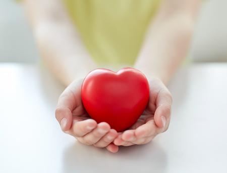 heart: persone, l'amore, la carità e concetto di famiglia - Close up delle mani del bambino che tiene a forma di cuore rosso a casa