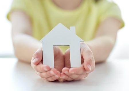 concept: le concept des gens, la charité, la famille et la maison - close up de fille heureux holding maison de papier découpée en mains évasées Banque d'images