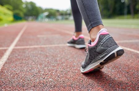フィットネス、スポーツ、トレーニング、人々 とライフ スタイル コンセプト - 後ろからトラックで実行されている女性の足のクローズ アップ 写真素材