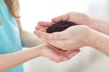 people, charity, family and legacy concept - close up of father and girl holding soil  in cupped hands at home Stock Photo