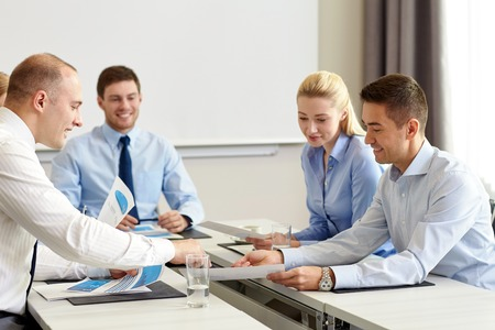 results: business, people and teamwork concept - smiling business team with papers meeting in office
