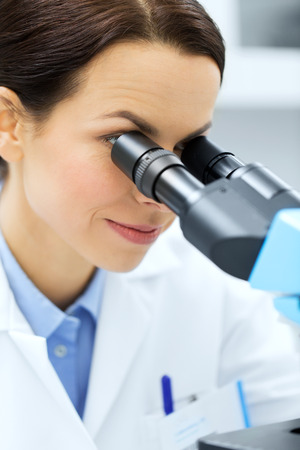 science, chemistry, technology, biology and people concept - close up of young female scientist face looking to microscope eyepiece and making or research in clinical laboratory